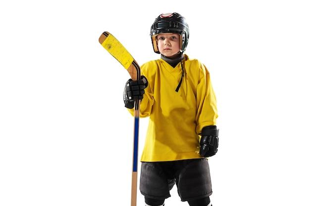 Pequeno jogador de hóquei com o taco na quadra de gelo e branco Foto gratuita