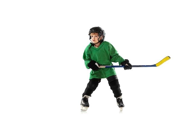 Pequeno jogador de hóquei com o taco na quadra de gelo, parede branca. desportista usando equipamento e capacete, praticando, treinando. conceito de esporte, estilo de vida saudável, movimento, movimento, ação.