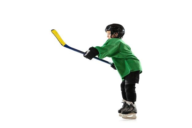 Pequeno jogador de hóquei com o taco na quadra de gelo, parede branca do estúdio