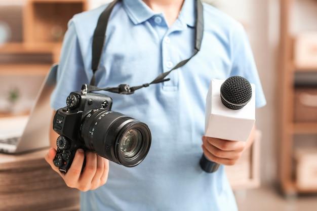 Pequeno jornalista com microfone e câmera no escritório