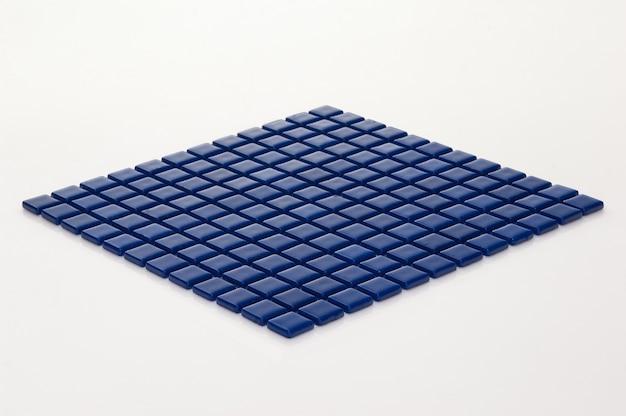 Pequeno ladrilho de cerâmica azul sobre um fundo branco, faiança. para o catálogo