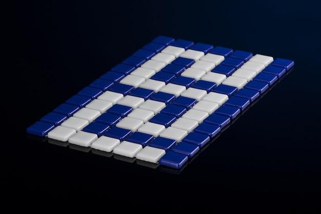 Pequeno ladrilho de cerâmica azul sobre um fundo preto, faiança. para o catálogo