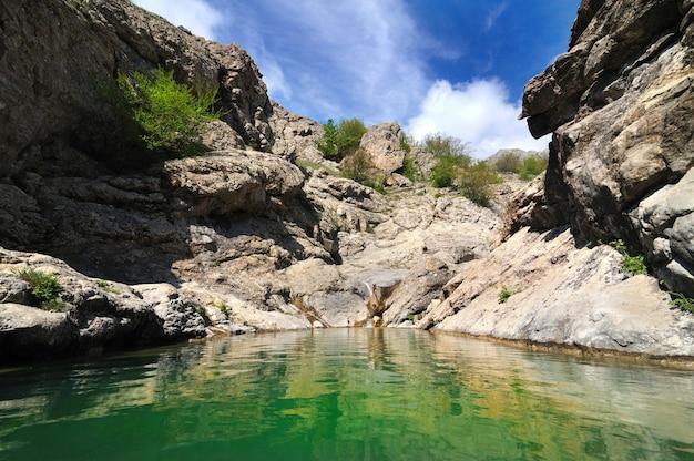 Pequeno lago entre montanhas com água verde brilhante. grama e arbustos crescem em pedras e rochas