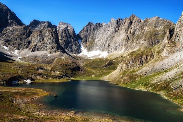 Pequeno lago se espalha contra o fundo das dolomitas em um dia quente de verão