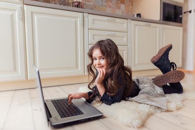 Pequeno lindo bebê caucasiano moreno deitado no chão na pele de animal artificial leve e assistindo desenhos animados no laptop com grande interesse.