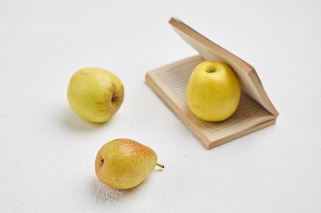 Pequeno livro aberto, maçãs e pêra mentem sobre uma superfície branca