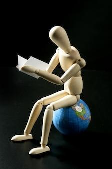 Pequeno manequim de madeira deading sentado sobre o mapa do mundo