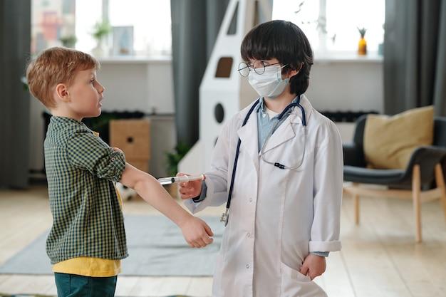 Pequeno médico de jaleco e máscara protetora fazendo injeção em um lindo garoto no jardim de infância