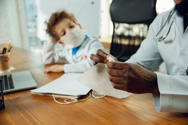 Pequeno médico durante a discussão, estudando com um colega mais velho