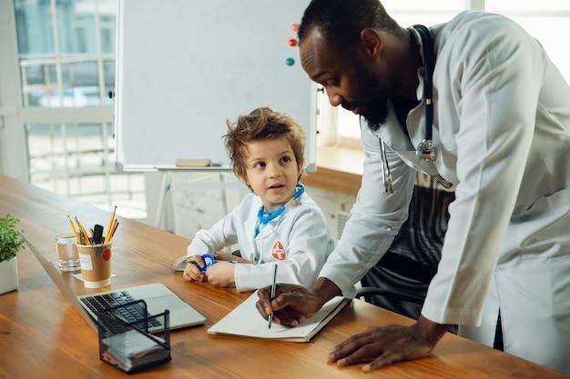 Pequeno médico durante o trabalho com um colega mais velho