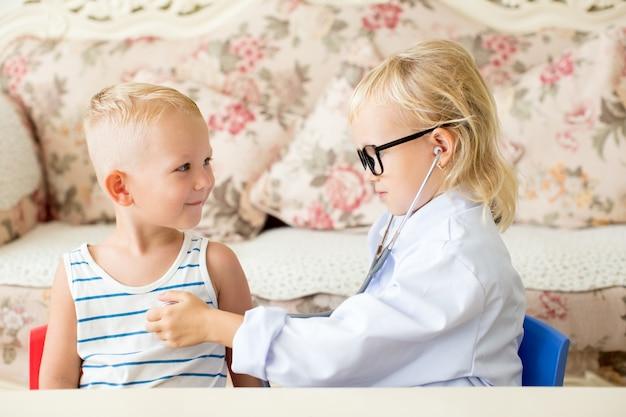 Pequeno médico sortudo examinando o paciente do menino