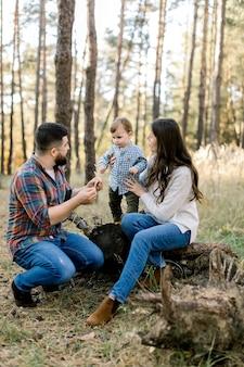 Pequeno menino adorável e fofo se divertindo enquanto se equilibra na árvore, segurando as mãos de sua mãe muito atraente e de seu pai barbudo bonito na floresta de outono ao ar livre
