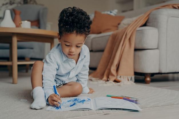 Pequeno menino africano sentado no chão e desenhando com caneta de feltro azul