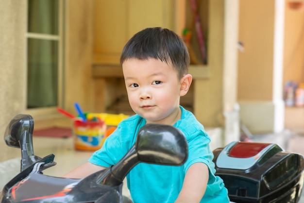 Pequeno, menino asiático, bicicleta equitação, brinquedo, inthe, casa, com, feliz, rosto