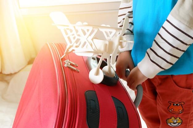 Pequeno menino asiático pronto para viajar com malas e seu avião de brinquedo, conceito de viagem e aventura