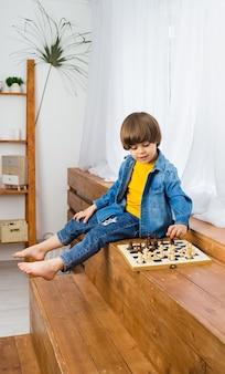 Pequeno menino caucasiano com cabelo castanho senta-se nos degraus e joga xadrez. desenvolvimento infantil