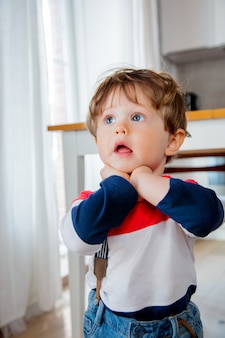 Pequeno menino todler ficar na cozinha em um dia
