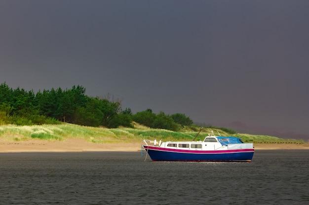 Pequeno navio de passageiros azul atracado na baía do mar báltico