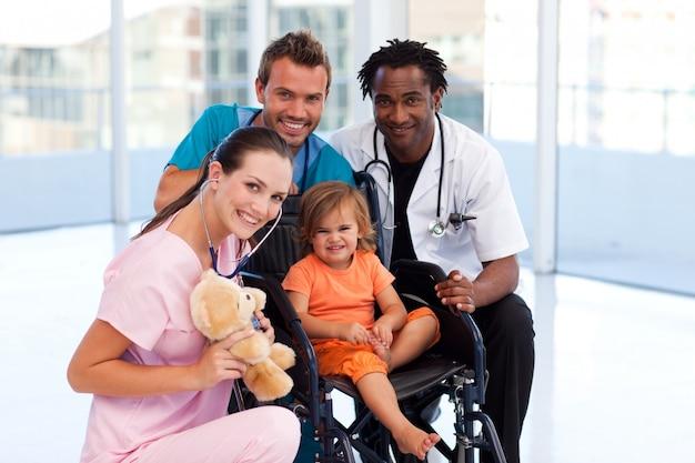 Pequeno paciente com equipe médica sorrindo para a câmera