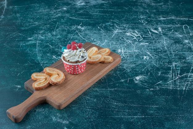 Pequeno pacote de biscoitos escamosos e um bolinho em uma placa sobre fundo azul. foto de alta qualidade
