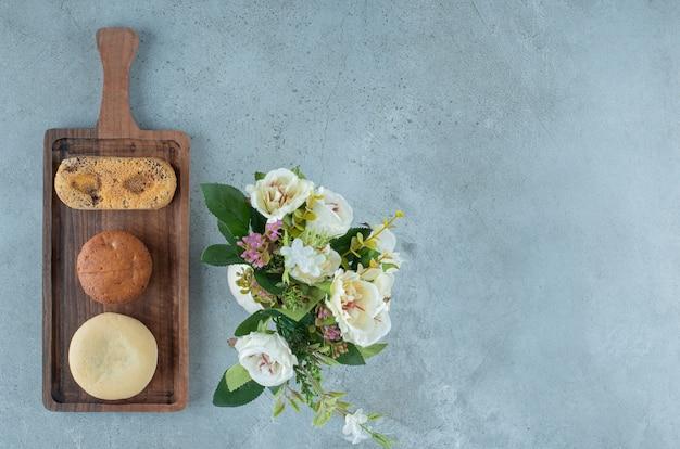 Pequeno pacote de bolos em uma pequena bandeja ao lado de um vaso de flores sobre fundo de mármore. foto de alta qualidade