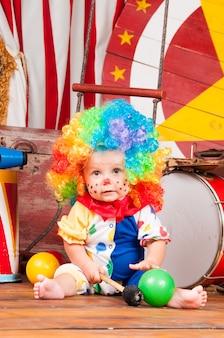 Pequeno palhaço bebê com peruca multicolorida de nariz vermelho com bolas.