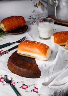 Pequeno pão pastoso longo servido com leite