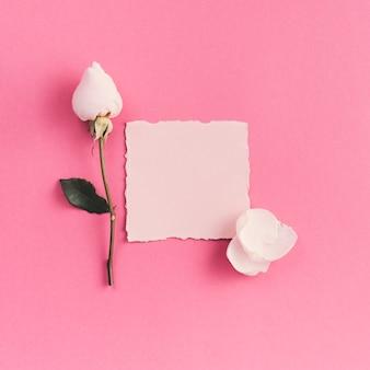 Pequeno papel em branco com flor branca na mesa