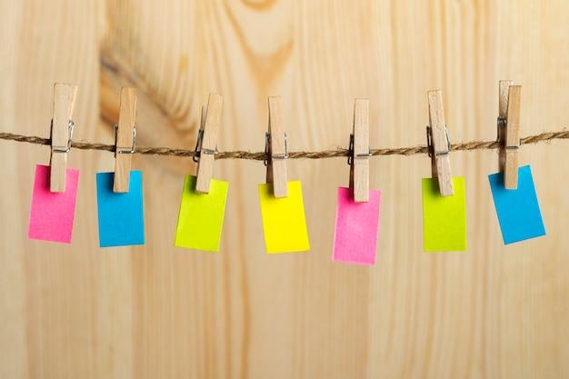 Pequeno papel heterogéneo com prendedores de roupa na corda. copie o espaço. lugar para o seu texto. nota, lembrete.