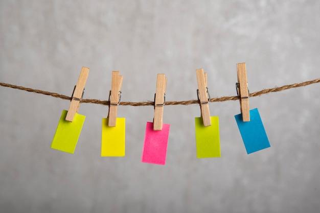 Pequeno papel multicolorido com prendedores de roupa na corda. copie o espaço. lugar para o seu texto. nota, lembrete.
