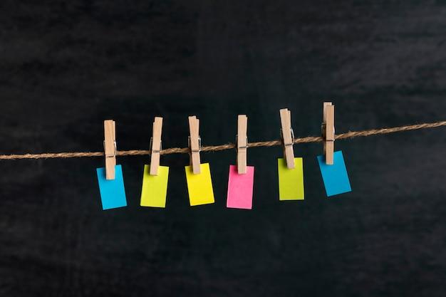 Pequeno papel multicolorido com prendedores de roupa na corda. fundo preto. copie o espaço. lugar para o seu texto. nota, lembrete.
