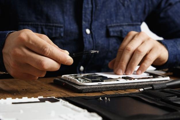 Pequeno parafuso em pinças em mão profissional reparando e consertando dispositivos eletrônicos quebrados no conceito de laboratório