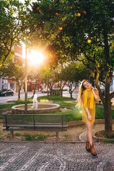 Pequeno parque com fonte e laranjeiras. linda garota com cabelo comprido, posando na rua.