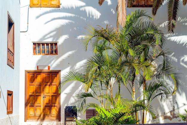 Pequeno pátio espanhol com palmeiras e banch. porta de madeira velha e janelas em garachico, tenerife, espanha