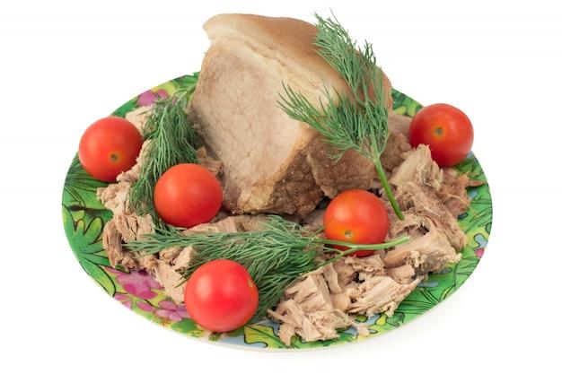Pequeno pedaço de carne de porco cozida em um prato com tomate cereja.