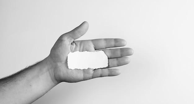 Pequeno pedaço de papel branco na mão do homem monocromático