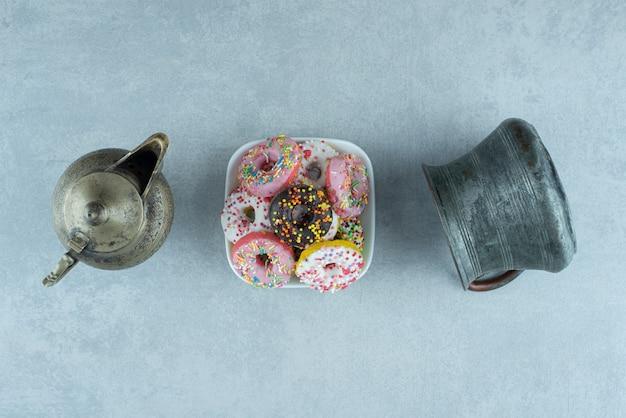 Pequeno prato de donuts entre um bule e uma jarra em mármore.