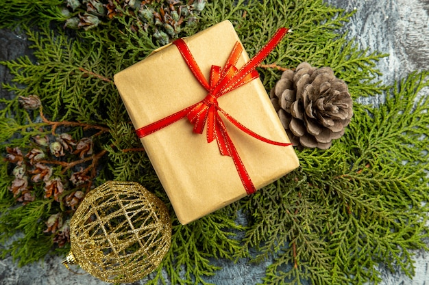 Pequeno presente amarrado com fita vermelha em ramos de pinheiro, pinha, presente de fundo