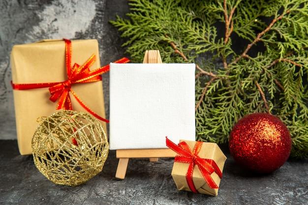 Pequeno presente de vista frontal amarrado com uma mini tela de fita vermelha em cavalete de madeira, ramos de pinheiro, bolas de natal em fundo cinza