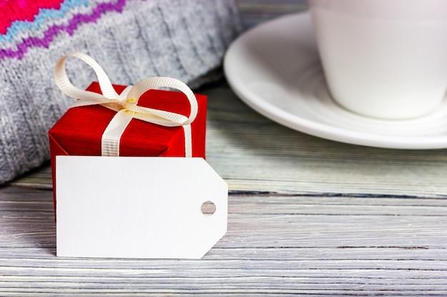 Pequeno presente vermelho e etiqueta de papel em branco sobre uma mesa de madeira clara. lugar para texto.