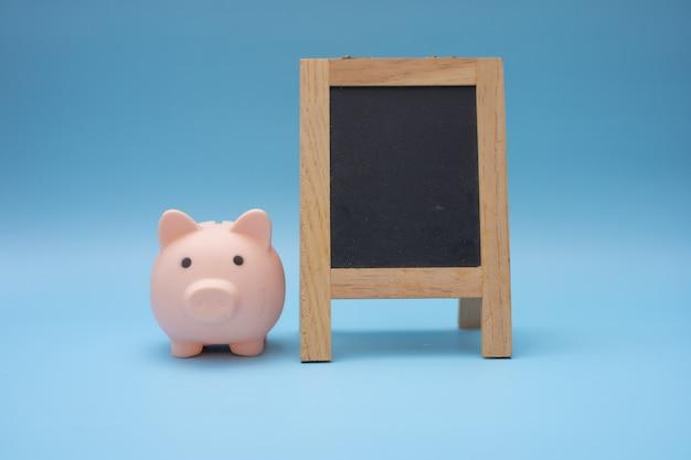 Pequeno quadro-negro com cofrinho, empréstimo para investimento empresarial vender o conceito imobiliário.