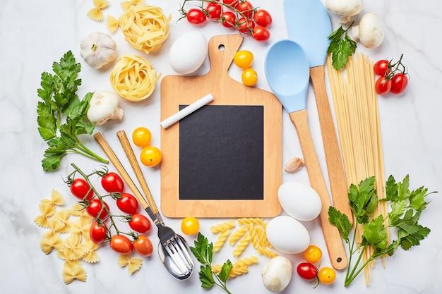 Pequeno quadro negro com espaço de cópia rodeado por ingredientes para cozinhar diferentes tipos de massas, condimentos, utensílios, vegetais crus saudáveis.