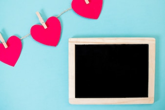 Pequeno quadro negro com festão de corações