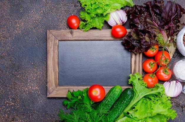 Pequeno quadro negro com legumes para salada ao redor