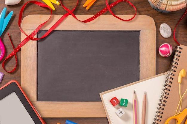 Pequeno quadro negro com material escolar na mesa de madeira