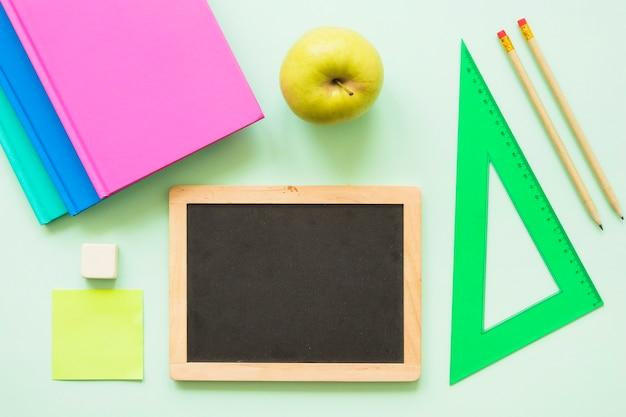 Pequeno quadro negro com papelaria e apple