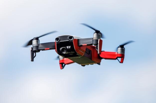 Pequeno quadrocopter vermelho no ar.