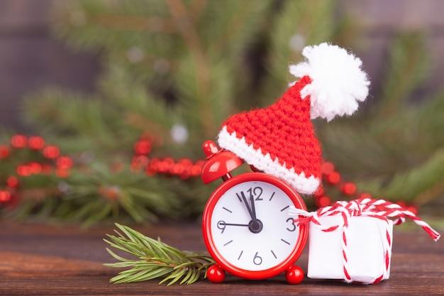 Pequeno relógio em um boné de natal.