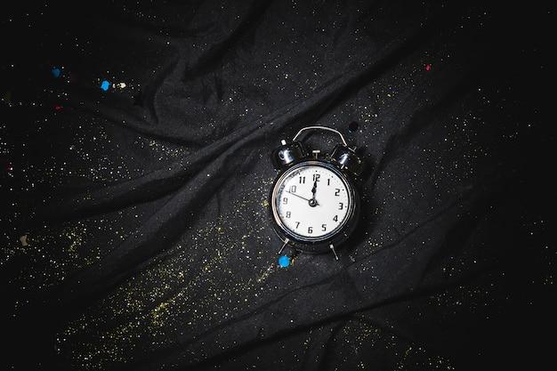 Pequeno relógio na mesa preta