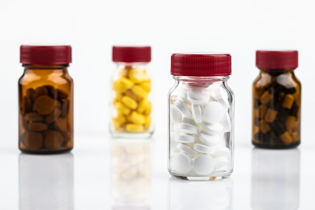 Pequeno remédio em frasco isolado no fundo branco